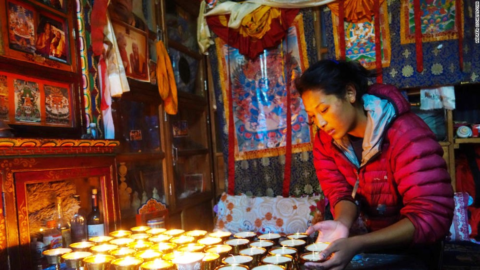 Butter lamps must remain lit throughout the 49-day period between lives (Bar-do), at the end of which the spirit of the deceased will reincarnate. The daughter of Ang Tshiring, Nima, attends to the butter lamps in the prayer room.