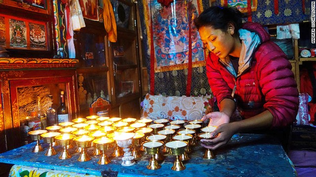 Ang Tshiring's daughter, Nima, attends to butter lamps in the prayer room.
