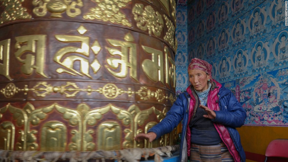 "Ang Riku spins a prayer wheel at Laudo monastery, repeating the mantra ""Om Mani Padme Hum"" to accumulate merit for her husband."