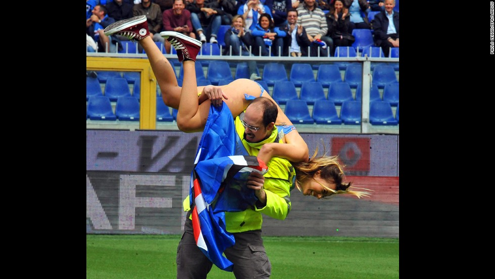 A steward carries a streaker from the pitch during the Italian Series A soccer match between UC Sampdoria and SSC Napoli at Luigi Ferraris stadium in Genova, Italy, on Sunday, May 11.