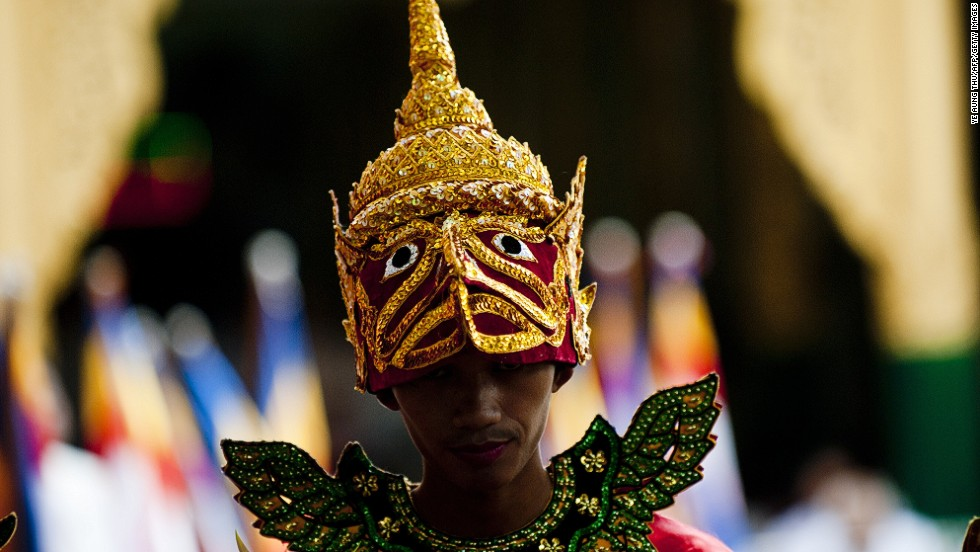 MAY 13 - YANGON, MYANMAR: A Buddhist devotee wears a traditional costume symbolizing a mythical bird at the Shwedagon Pagoda on the full moon day of the Kasone Festival to mark Buddha's birthday. The festival commemorates the anniversary of the birth, enlightenment and death of Shakyamuni Gautama Buddha.