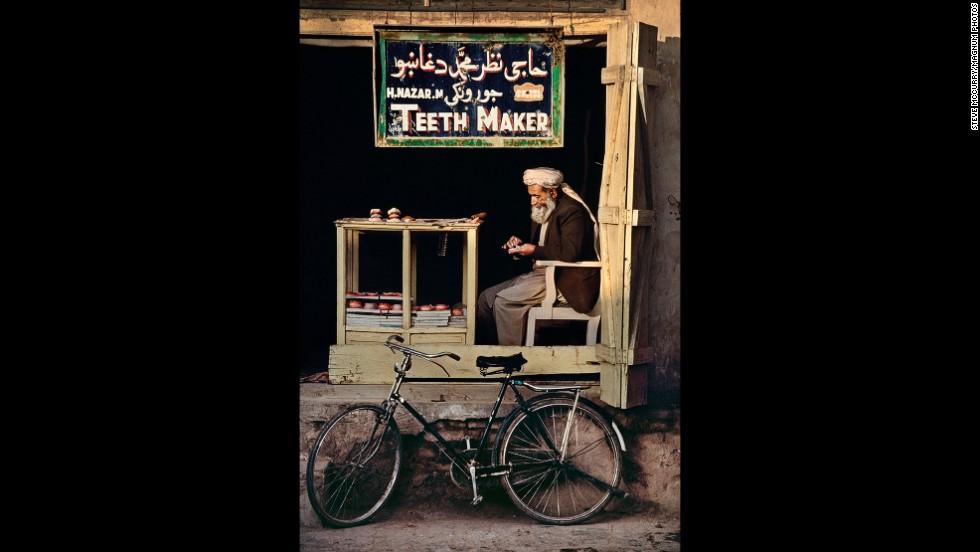 An Afghan teeth-maker sits in a makeshift shop in Kandahar, 1998.