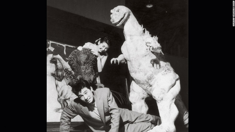 """Godzilla"" stars Akira Takarada, bottom, and Momoko Kochi clown around at Toshimitsu's fabrication studio with the unfinished monster costume in 1954."
