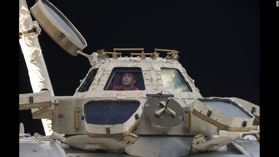 Commander Koichi Wakata of the Japan Aerospace Exploration Agency peers out of the space station's Cupola observatory on April 27. The Cupola is a dome-shaped module that allows station crew members to observe and guide activities outside the station.
