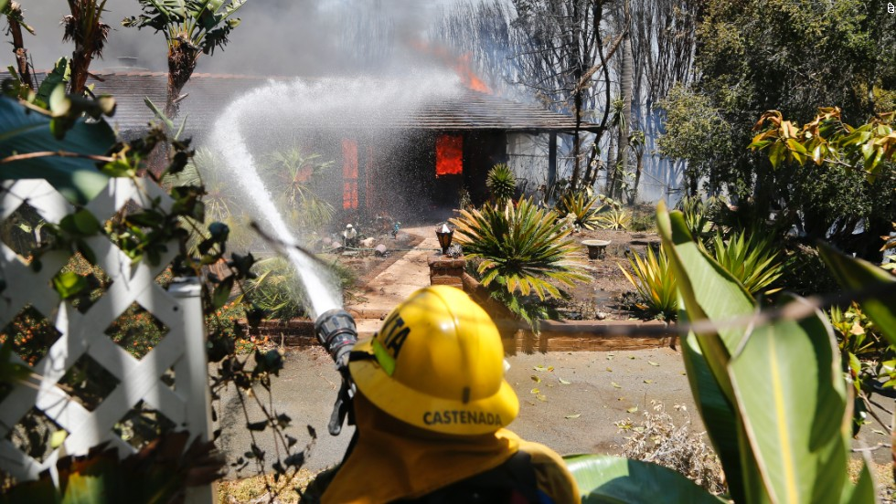 A firefighter sprays water onto a fully engulfed home in Carlsbad on May 14.