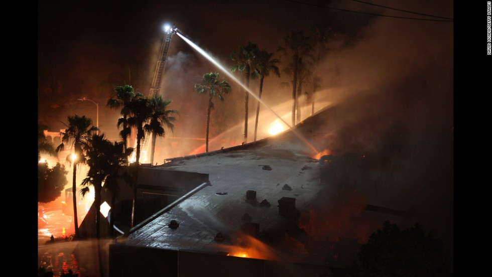 Firefighters spray water on a burning building in Carlsbad, California.