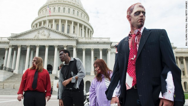 Zombies stumble across the East Plaza of the U.S. Capitol to promote 'The Warehouse: Project 4.1' urban haunted house in Rockville, Maryland, on Wednesday, October 3, 2012.