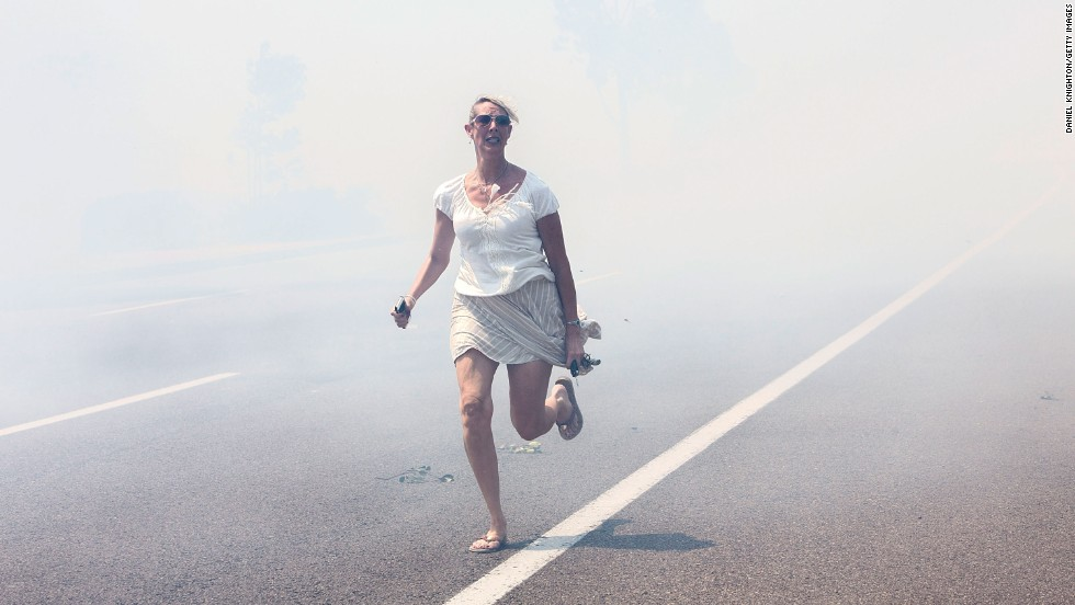 "A woman flees a wildfire as it crosses a highway in Carlsbad, California, on Wednesday, May 14. <a href=""http://www.cnn.com/2014/05/13/us/gallery/california-wildfire/index.html"">Wildfires have forced evacuations</a> in San Diego County after a high-pressure system brought unseasonable heat and gusty winds to the parched state."