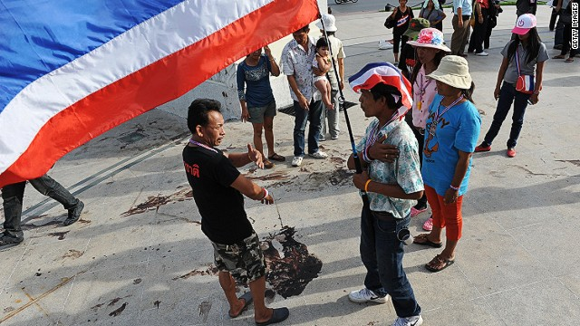 BANGKOK, THAILAND - MAY 15: Protesters and bystanders gather at the scene of a deadly drive-by attack on an anti-government rally site at the landmark Democracy Monument on May 15, 2014 in Bangkok, Thailand. Unidentified assailants on a pick-up truck attacked the protest site overnight with a grenade and gunfire, killing three protesters and wounding over 20. The attack came amid fears of violence between rival pro and anti-government groups in Thailand's ongoing political turmoil. (Photo by Rufus Cox/Getty Images)