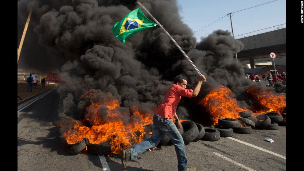 A member of the Homeless Workers Movement carries a Brazilian flag past burning tires near Itaquerao Stadium, which will be used during the World Cup in Sao Paulo.
