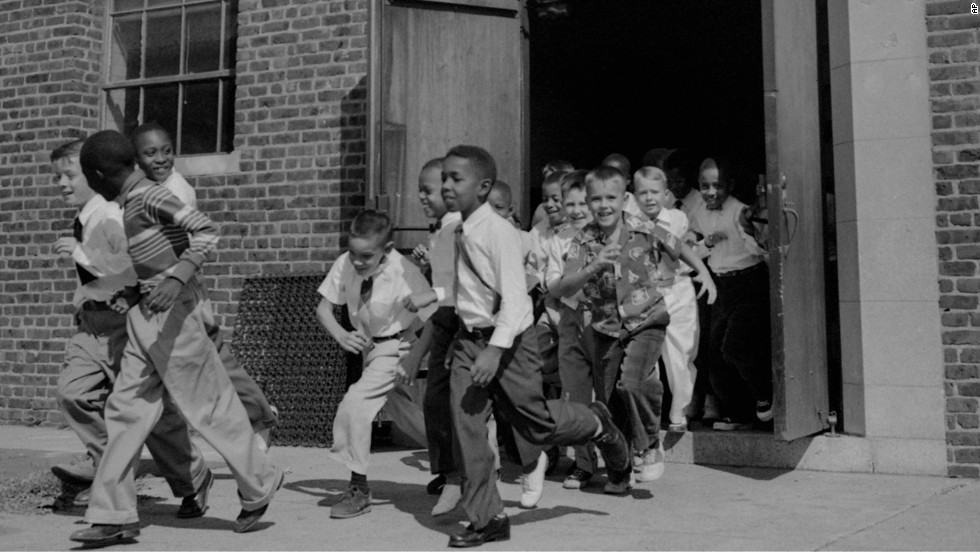 "Fourth-graders, both black and white, dash for the playground at St. Martin School in Washington on September 17, 1954. The Supreme Court ruling did not set a schedule for the integration of schools, rather calling for ""deliberate speed."" The District of Columbia and four states acted to end segregation promptly, while other areas met with resistance."