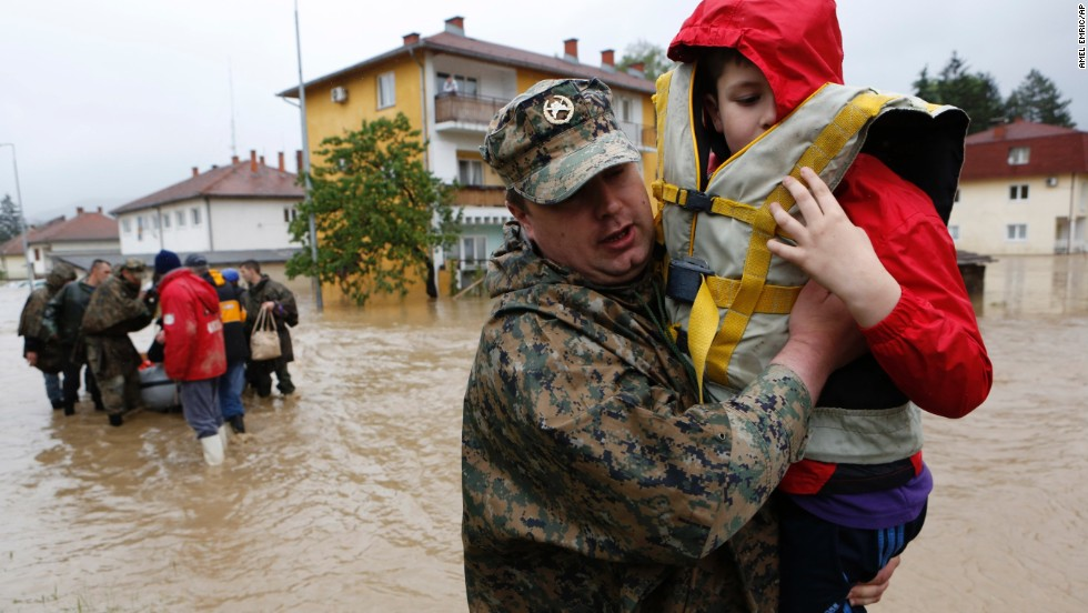 A member of the Bosnian army carries a boy rescued from his home May 16 in the town of Maglaj.