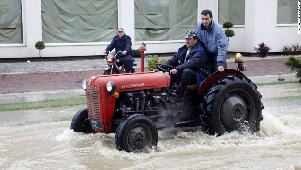 Bosnian men ride a tractor through flooded streets of Banja Luka on May 17.