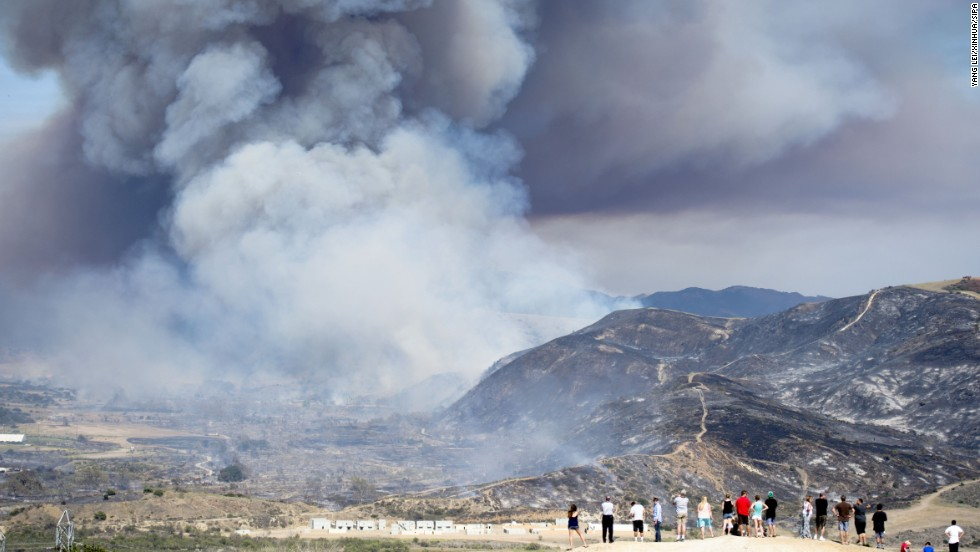 Residents watch a wildfire near San Diego on Friday, May 16. Wildfires devoured more than 20,000 acres in San Diego County after a high-pressure system brought unseasonable heat and gusty winds to the parched state.