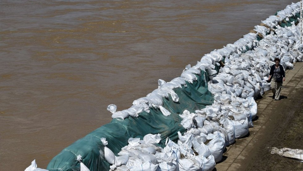 A woman walks past sandbags along the banks of the Sava River, in the Serbian city of Sremska Mitrovica on May 18.
