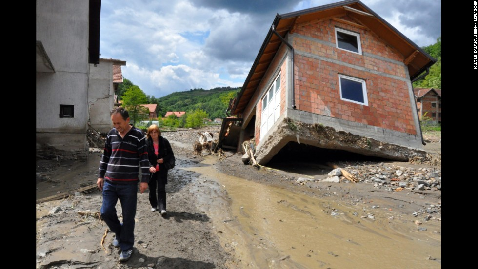 People walk past damaged houses in Krupanj on Sunday, May 18.