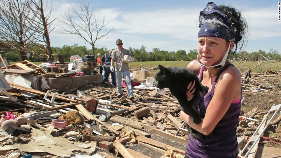 <strong>Then:</strong> Brittany Brown rushes to get aid after finding her grandmother's cat, Kitty, on May 22, 2013. The cat was buried in the rubble for two days.