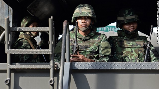 Thai army soldiers sit in a truck outside the compound of the National Broadcasting Services of Thailand after martial law was imposed in Bangkok on May 20, 2014.