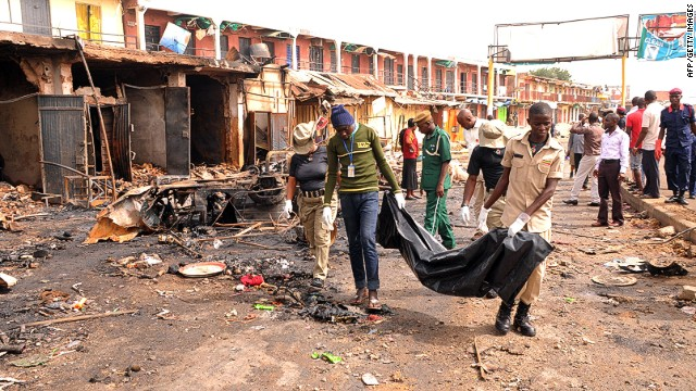 "Rescuers carry a body recovered from a burnt shop at the scene of twin bomb blasts at terminus market in the central city of Jos on May 21, 2014. Twin car bombings in central Nigeria killed at least 118 people and brought entire buildings down Tuesday, in the latest affront to the government's internationally-backed security crackdown. Nigerian President Goodluck Jonathan swiftly condemned the attack in the central city of Jos, calling it a ""tragic assault on human freedom"" and condemning the perpetrators as ""cruel and evil"". AFP PHOTO/ STRSTR/AFP/Getty Images"