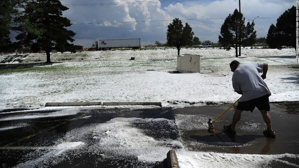 Rob Post sweeps hail in Woodshire Mobile Park in Aurora on May 21.