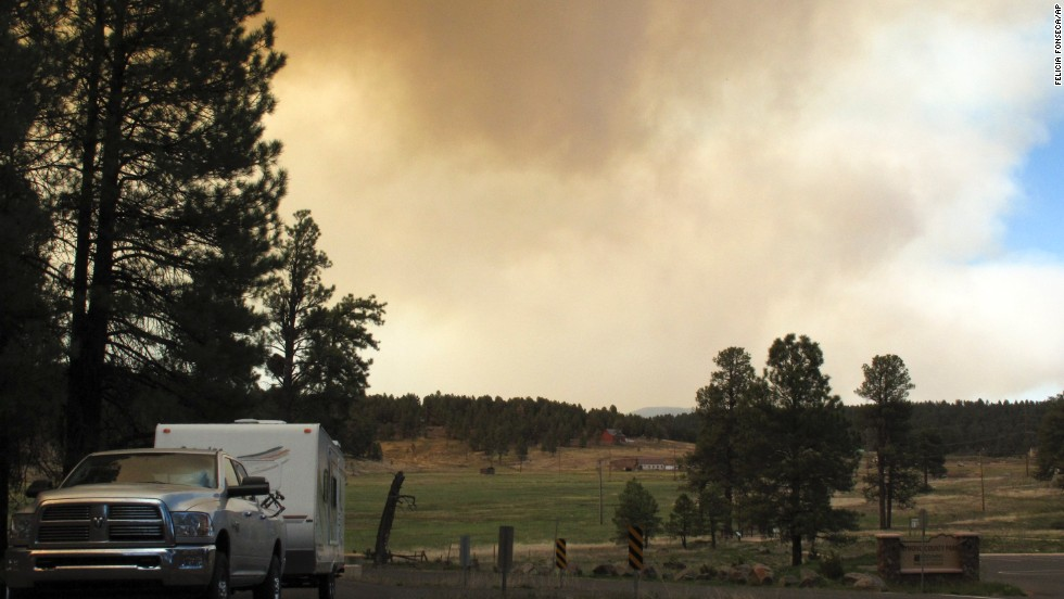 A vehicle heads out of Kachina Village as the wildfire sends plumes of smoke into the air on May 21.