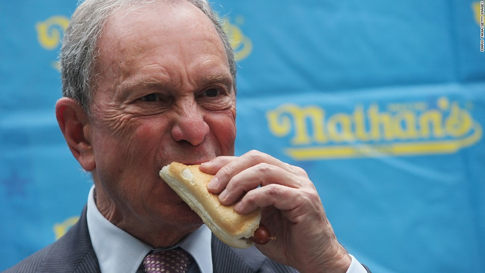 Then-New York Mayor Michael Bloomberg eats a hot dog at the weigh-in ceremony for the Nathan's July Fourth contest in 2013.