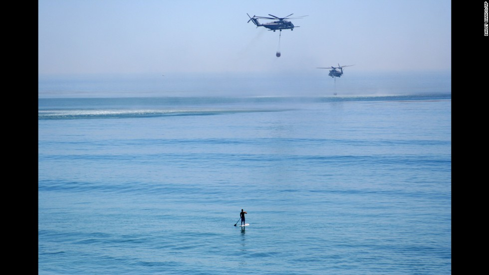 "A paddleboarder watches two helicopters grab water from the Pacific Ocean to fight wildfires near Camp Pendleton, California, on Friday, May 16. Wildfires <a href=""http://www.cnn.com/2014/05/13/us/gallery/california-wildfire/index.html"">devoured more than 20,000 acres</a> in San Diego County after a high-pressure system brought unseasonable heat and gusty winds to the parched state."