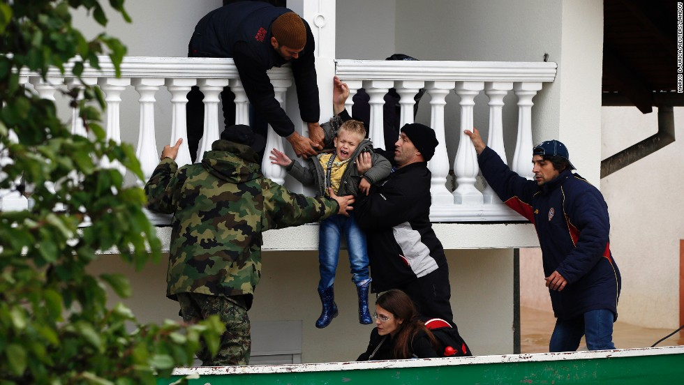 "Serbian soldiers rescue a boy from a flooded house in the town of Obrenovac on Saturday, May 17. Heavy rainfall in Serbia and neighboring Bosnia-Herzegovina has resulted in <a href=""http://www.cnn.com/2014/05/16/europe/gallery/balkans-flooding/index.html"">the worst flooding since records began 120 years ago</a>, meteorologists say."