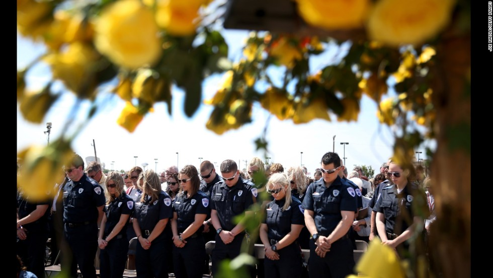 """First responders bow their heads in prayer on Tuesday, May 20, during the remembrance ceremony for those killed by last year's <a href=""""http://www.cnn.com/2014/05/20/us/gallery/moore-oklahoma-then-now/index.html"""">tornado in Moore, Oklahoma</a>. The tornado killed 24 people and caused an estimated $2 billion in property damage. <a href=""""http://www.cnn.com/2014/05/16/world/gallery/week-in-photos-0516/index.html"""">See last week in 37 photos</a>"""