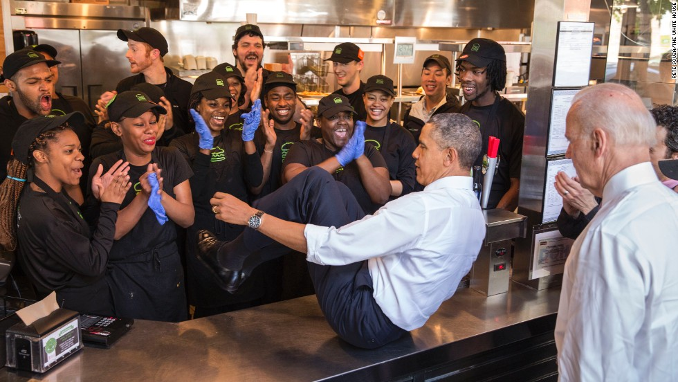 In this photo released by the White House, U.S. President Barack Obama slides across a counter to pose with staff members at a Shake Shack restaurant in Washington on Friday, May 16. Vice President Joe Biden, lower right, also did the same.