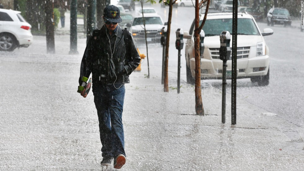 Robert Teran walks to work as hail falls over downtown Denver on May 22.