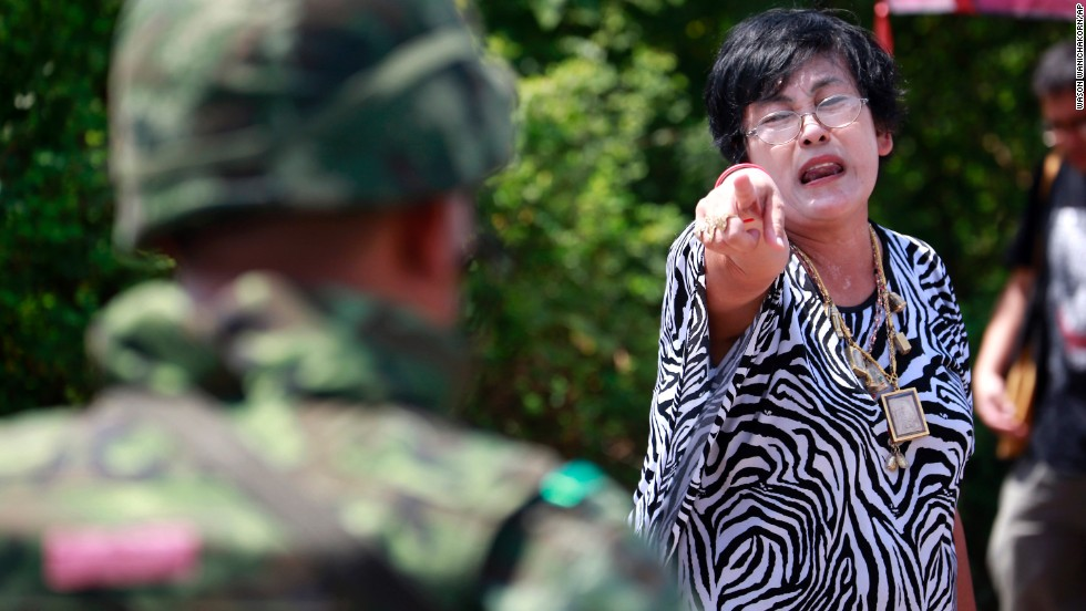 A pro-government protester points at a soldier as people clean up a demonstration site on the outskirts of Bangkok on May 23. Both pro- and anti-government camp sites have been cleared away in the capital city since the coup.