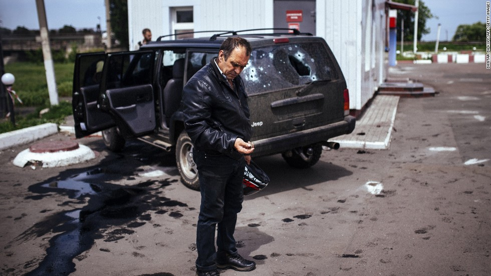 A man looks at a bullet shell next to a destroyed car after a gunfight between pro-Russian militiamen and Ukrainian forces in Karlivka, Ukraine, on Friday, May 23. Much of Ukraine's unrest has been centered in the Donetsk and Luhansk regions, where separatists have claimed independence from the government in Kiev.
