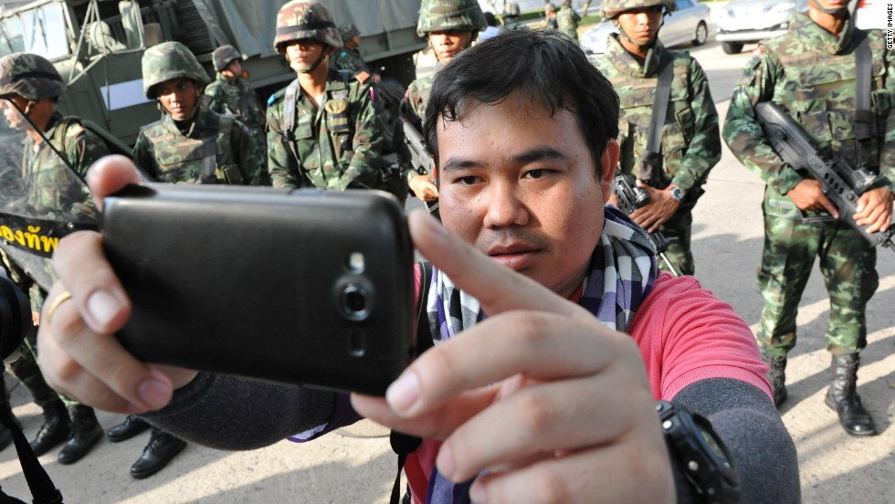 A member of the press takes a selfie with soldiers on May 22 in Bangkok.