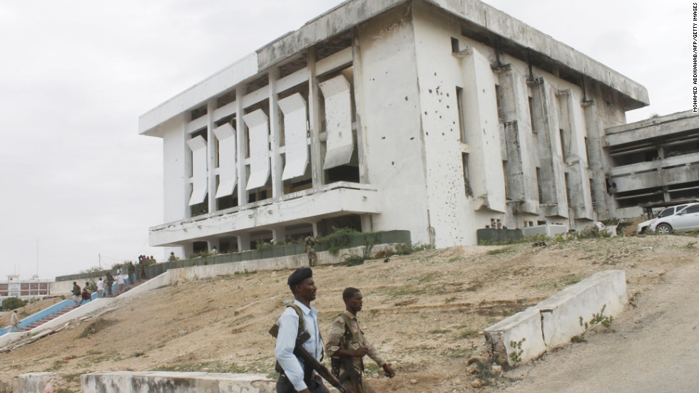 Somali army soldiers walk next to the parliament building after the attack.