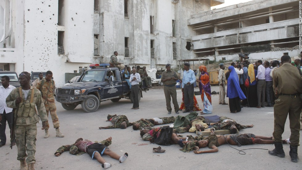 People gather around the bodies of combatants after the attack.