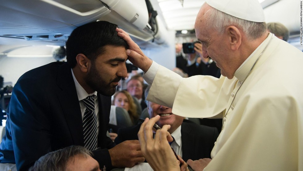 Pope Francis blesses a man as he greets journalists aboard the papal flight on his way to Jordan on May 24.