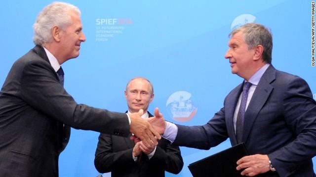 Putin behind Igor Sechin (R), the CEO of Rosneft, and Marco Tronchetti Provera of Italian tire manufacturer Pirelli.