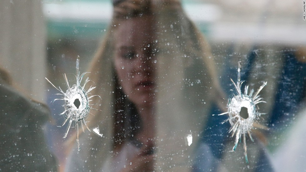 A woman looks at the bullet holes on the window of the deli where part of the shooting spree took place in Isla Vista, California.