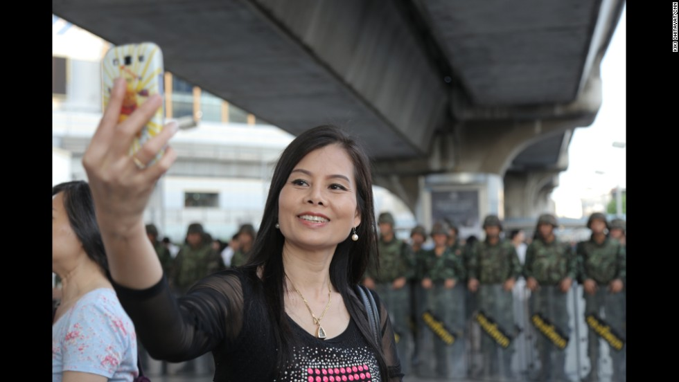 A woman takes a selfie in front of army soldiers standing guard in Bangkok, Thailand, on Saturday, May 24. Thailand's military declared last week that it had taken control of the country in a coup.