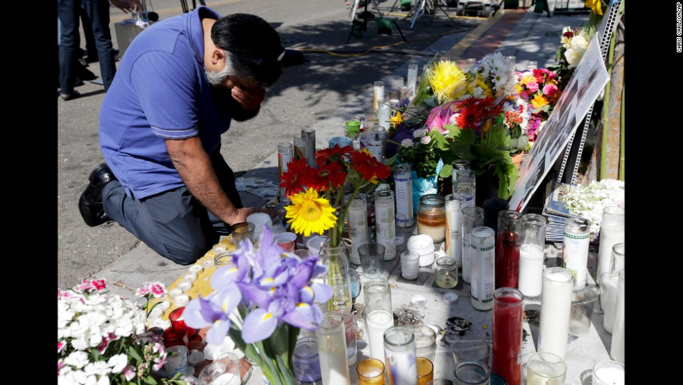 Jose Cardoso pays his respects Sunday, May 25, at a makeshift memorial at the IV Deli Mart, where part of a mass shooting took place, in Isla Vista, California. Elliot Rodger, 22, went on a rampage Friday night, May 23, near the University of California, Santa Barbara, stabbing three people to death at his apartment before shooting and killing three more in a nearby neighborhood, sheriff's officials said. Rodger also injured 13 others and died of an apparent self-inflicted gunshot wound, authorities said.<br />