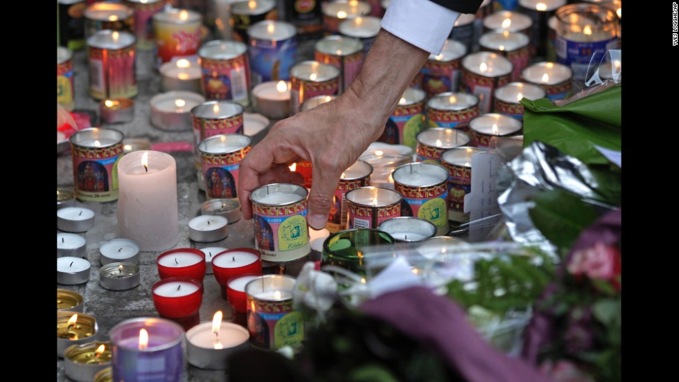 A man places a candle in front of the entrance of the museum on May 25.
