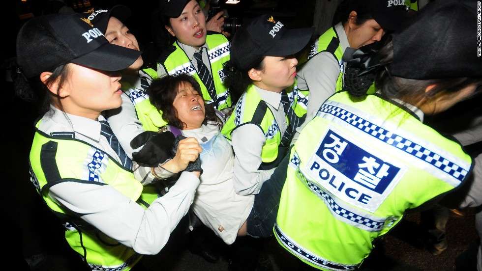 Police in Seoul detain a protester during a march Saturday, May 17, for victims of the Sewol.