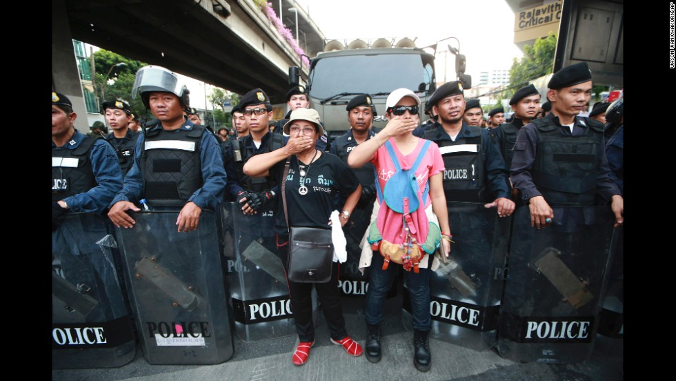 Two protesters stand in front riot police during an anti-coup demonstration in Bangkok on Monday, May 26. Demonstrators have taken to the streets in opposition to the coup, while some Thais express hope the military will bring an end to the political crisis.