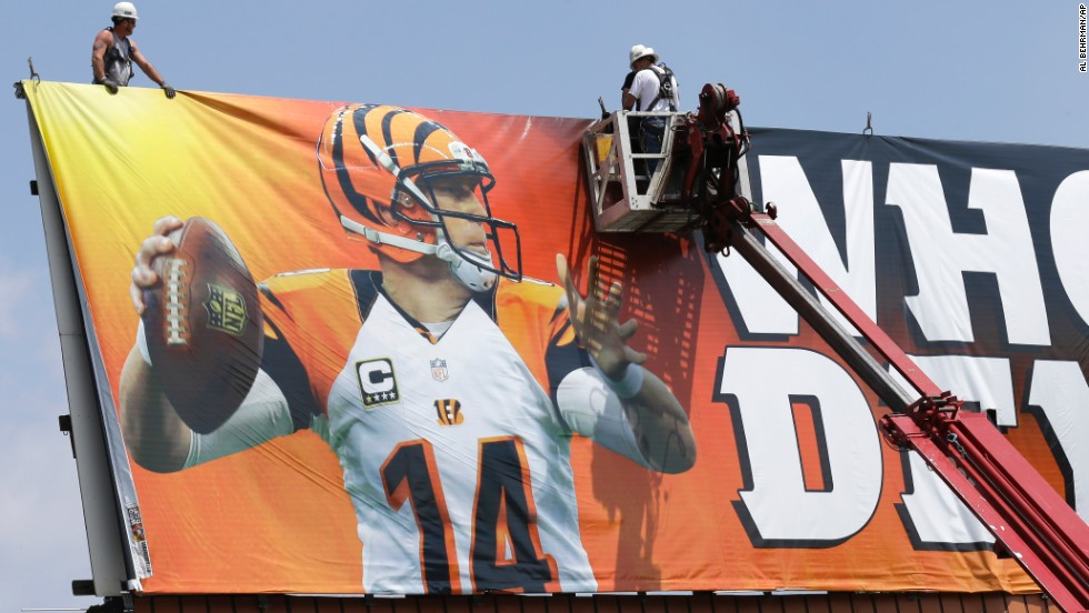 Workers in Covington, Kentucky, stretch out a billboard showing Cincinnati Bengals quarterback Andy Dalton on Thursday, May 22.