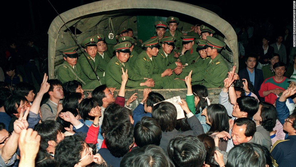 May 20, 1989, pro-democracy demonstrators raise their fists and flash the victory sign while stopping a military truck filled with soldiers on its way to Tiananmen Square.