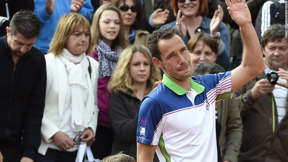 Frenchman Michael Llodra waves goodbye to the crowd with his young son after defeat to Fernando Verdasco in his last professional match at Roland Garros.