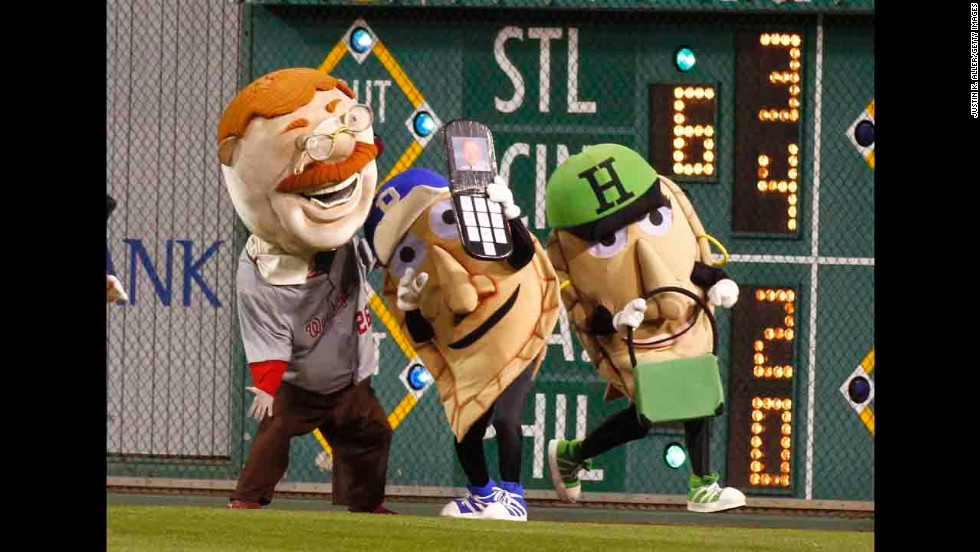 Potato Pete pretends to take a selfie with fellow mascot Teddy Roosevelt as Jalapeno Hannah, right, races by Friday, May 23, at a Major League Baseball game in Pittsburgh.