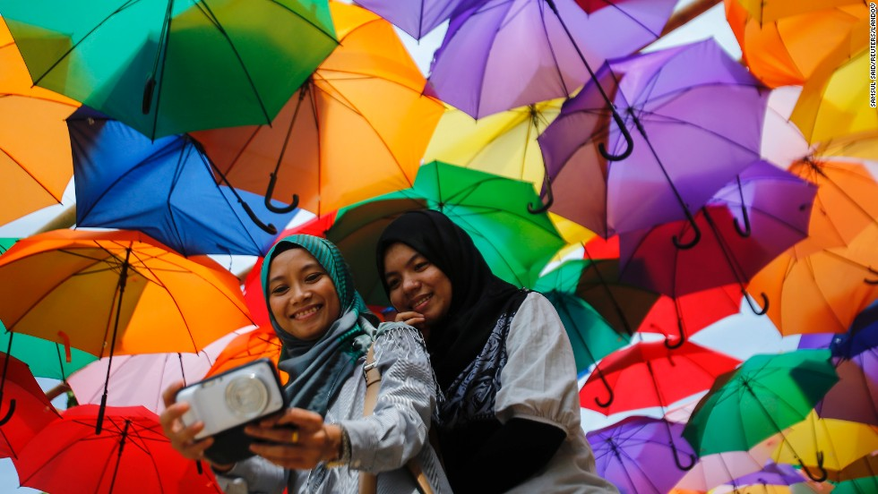 Women take a selfie near an installation of colorful umbrellas Friday, May 23, at the Putrajaya Youth Festival in Putrajaya, Malaysia.