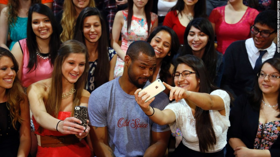 "Isaiah Mustafa, who appeared in a series of popular commercials for the company Old Spice, poses with students at Morton West High School during an Old Spice promotional stop Friday, May 23, in Berwyn, Illinois. The assembly taught students to ""scent responsibly."""